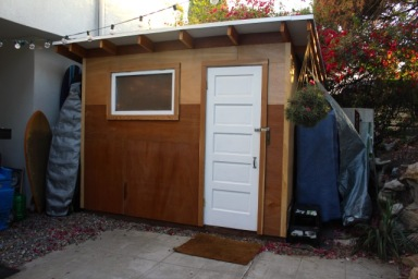 "Shed by Ron and George, Hollywood, CA: ""Your plan was so helpful in getting us to think about the right things and do them in the right order. This is 10' x 8' with Home Depot lumber. The facade is completely reclaimed. We found the pebbled window in a salvage yard for $30 and the tu-tone luan and door came from a gut job in Hollywood next door to my son's actor friend. We found a pile of bright blue painted plywood that someone had used as a blue screen studio in the garage, but on the flip side was pristine luan, that makes good siding with enough battens behind it... My son is now using this place as an music and audio post studio, and it's really allowed him to get stuff done."""